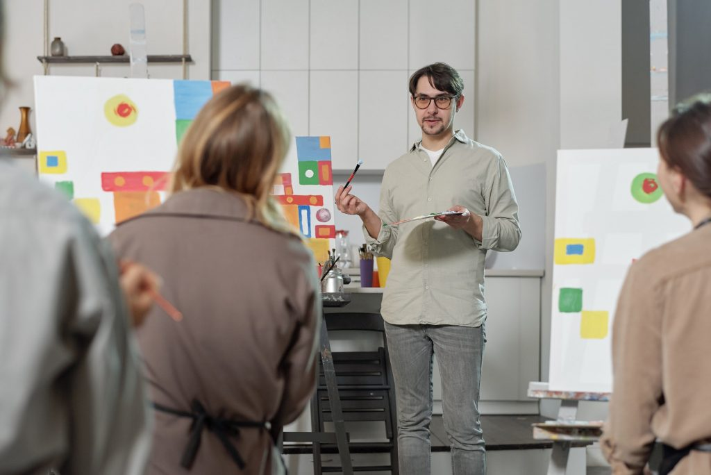 Confident teacher of painting explaining his students main rules of drawing